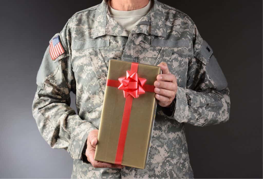Closeup of a soldier or military personnel holding a Christmas present. The gift is wrapped in gold paper with red ribbon and bow.
